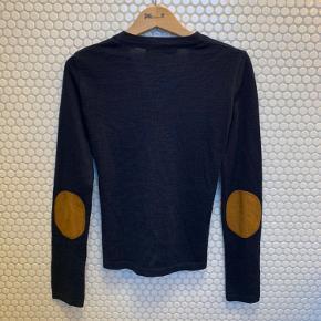 Cardigan fra Sibin Linnebjerg i marine blå, med brun ruskind lapper på albuerne.  50 % merino uld, 50 % akryl. Så god som ny