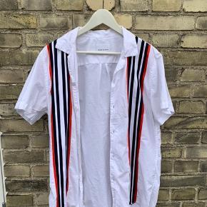 Samsoe & samsoe kortærmet skjorte i hvid med røde og sorte striber, perfekt til sommeren Str L. Brugt meget få gange, og sælges grundet mistet interesse.  Betaling foregår via tradono eller mobilepay.