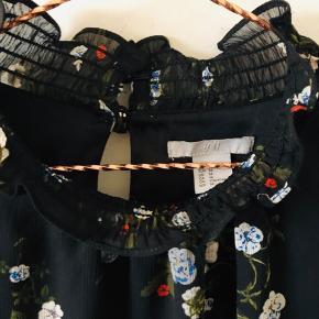 Superfin tunika med detaljer og blomster