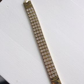 Flot armbånd fra Dyrberg/kern.  Guldfarvet med klare swarovskisten  Nypris: 849kr Sælges for 375kr plus porto