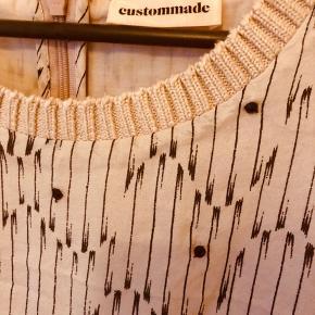 Sød rosa kjole fra Custommade med poseeffekt på overstykket og små påsyede sorte perler ved brystet,