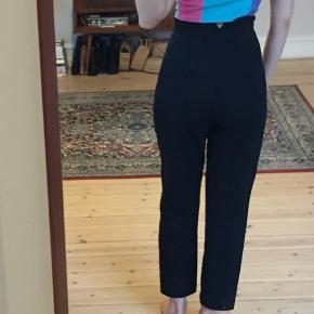 Højtaljede sorte bukser fra H&M. Har folder ved taljen på front og lomme i hver side. Str. 34. God stand!