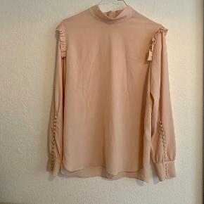 Lyserød bluse med fine detaljer og små knapper på ærmerne