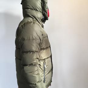 Super fed vinter/skijakke + skibukser fra italiensk Moncler. Begge dele er fra Grenoble skiwear kollektionen og jakken er lavet af 90%dun og 10%fjer.  Indvendig snowskirt, stor hætte, lynlåse i siden og på den ene arm.  Skibukserne har lynlåsfunktion, så man kan åbne dem helt op på begge bukseben. Nederst på det ene ben er der kommet en rift i stoffet , men den kan repareres.