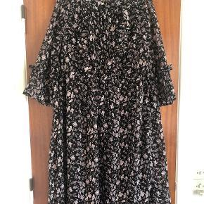 Fin kjole med fine detaljer, og sort underkjole. Flæser på brystet og bindebånd i taljen.