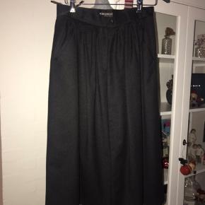 Super smuk nederdel i uld. Den har fine detaljer foran såsom læg og lille lomme. Den lukkes med knap og lynlås foran. Den er fra mærket Widudress Taljemål 40 cm (x2) Længde 80 cm Mp 210 kr pp
