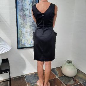 Smuk sort kjole med foer og små læg og store lommer fortil og en sort lynlås bag og en lille slids forneden. Kjolen er brugt få gange og fremstår som ny. Til salg i flere grupper!