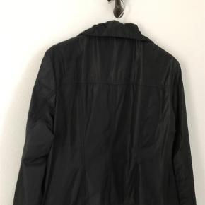Varetype: Indendørsjakke Størrelse: 44 Farve: Sort Oprindelig købspris: 999 kr. Kvittering haves.  Jakken er helt sort, men nogle foto er taget i modlys for bedre at kunne se detaljerne. 100 % polyester, som er elastisk. Længde under krave 60 cm. Bryst 52 x 2. Skulder til skulder 44. Ærme fra skuldersøm 58 cm. Virkelig lækker jakke. Har nederdel til salg, som er købt dertil, selv om den er fra Carla du nord.