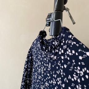Nr 105  En fin blomstret kjole fra Moss Copenhagen. Materialet er 100% Viskose. Farven er Navy med hvidt blomstermønster.  Byd endelig - og husk at tjekke mine andre annoncer igennem 😉  Vi kan mødes og handle i København ellers sendes varen med DAO på købers regning 🕊