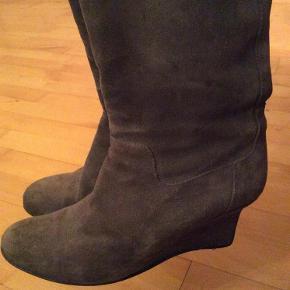 I pæn stand. Det ses dog selvfølgelig på ruskindet og hælene, at de er brugt (se billeder).  Indvendig diameter på støvlerne øverst på skaftet: Ca. 35,5 cm. - Højde på hælen: Ca. 7,5 cm. - Længde på skaftet bagerst fra fodens hæl og op: Ca. 30 cm.   Du er meget velkommen til at hente dem i Odense V :)    Sig endelig til, hvis du har spørgsmål.  Lange støvler ruskind kilehæl Farve: Grå
