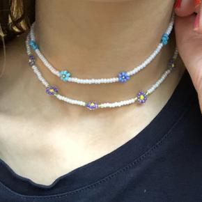 Hvid perle halskæde med 3 forskellige blå blomster Eller lilla blomster 💮 Prisen er inkl Porto - tá gerne to halskæder med blomster for 100kr inkl Porto.