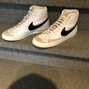 Sælger disse Nike BLAZER MID '77 i str 43   Som i kan se på billeder så er den ene lille flab på den ene sko gået i stykker, men er sikker på at man bare kan sy den på igen hvis det er. Og så er der også lidt rødt ude på enden af den ene sko, men det er meget utydeligt, men det er der.   BYD