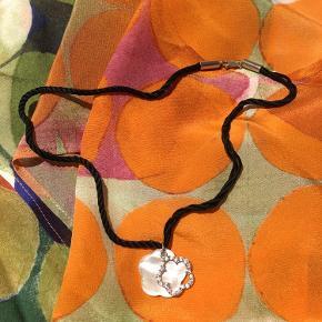 Så smuk halskæde.  Firkløver i perlemor. Sølvfarvet blomst med stene.  Sort snor med lukkemekanisme.  Aldrig brugt.  Kommer i original smykkepose.