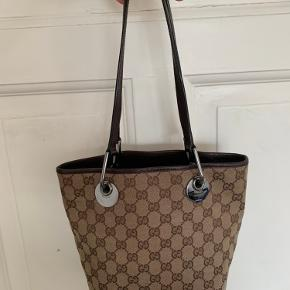 Så smuk vintage Gucci taske - købt i vintage butik med mærkevarer - BEMÆRK: jeg har ikke kvittering på tasken. Tasken er ca 17 cm lang og 25 cm høj(målt uden stropper) -personen på billedet er 178 cm høj og en str L/XL.  Tasken er brugt og har lidt slid, men faktisk i fin stand. Se billeder for at se slid. Pris 1800kr - jeg er åben for SERIØSE bud omkring de 1800kr. Men hvis ikke det rette bud opnåes forbeholder jeg mig retten til at beholde tasken. BYD venligst kun hvis du er en seriøs køber