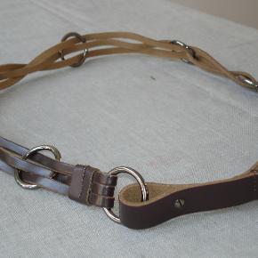 Anderledes, mørkebrunt læderbælte med flettede læderremme og metalringe i størrelse L/XL fra Bitte Kai Rand. Bæltet skal hænge løst. Måler 105 cm. Aldrig brugt. BYTTER IKKE!