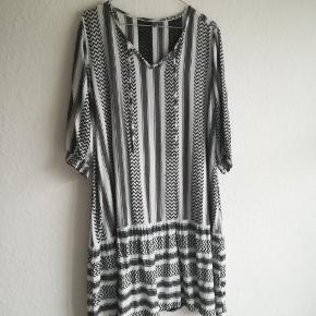 Fin kjole i 100% viskose. Har lidt små tråde der er gået, men kun noget der er synligt når man kommer tæt på. Derudover er den begyndt at fnulre lidt enkelte steder, men jeg vil mene den stadig har en god levetid 😊
