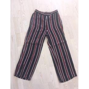 Stribede bukser fra H&M. Navy, hvid og røde farver. 90% viskose. Med lynlås, hægter og knapper. Elastik bagpå i talje. Baglommer. Fejler intet.