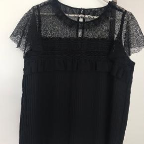 Sød t-shirt fra ZARA. T-shirten har både blonde og plisseringer. Fremstår helt ny.