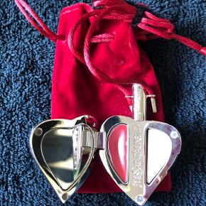 Sjælden YSL samlerobjekt sælges! Måler ca. 7 x 5 x 3 cm. Smukkeste hjertemedaljon med røde sten. Indeholder spejl i den ene side og to stk. ubrugte lip-glosses i den anden side.  Pensel sidder et rør i toppen af hjertet! Der medfølger fin rød velour-pose! Hjertet er selvfølgelig 100% ægte YSL! Købt i Magasin i 2008, og aldrig brugt.