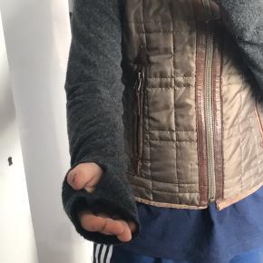 """Den kan både være """"jakke"""" og vest. Ærmerne kan tages af via en lynlås (skriv privat for flere billeder). Læderet og lynlåsen er det eneste der har tegn på slid. BYD gerne  Main fabric: 100% polyester  Sleeve fabric: 49% acrylic 30% polyester 21% wool  Trim fabric: 97% cotton 3% elastane Trim leather: 100% lamb leather  (Den er 68cm fra kraven og ned)"""