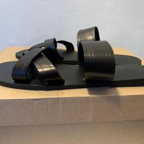Sorte lette skind sandaler (slider model) i str. 39 (lidt små i str., Så vil mene de passes af 38,5, så det har jeg sat dem til i str.feltvælger)  Har dem også i 37,5/(38) - se anden annonce) Mål fra hælkant til snude ca 26 cm NB: de sidder ret godt på foden ift remme - ikke bred model! De sidste tre billeder r fra nettet' Nypris 380,- og sælges for 1/2 pris.