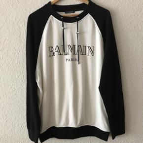 Cool ikonisk sweatshirt fra Balmain i hvid/sort. Fantastisk blød og behagelig at have på. Den er brugt én gang til et speciel arrangement og er derfor næsten som ny. Købt i butikken i Paris og kostede 4.200kr