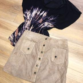 Lækker kort beigefarvet nederdel med knapper foran fra Margit Brandt i ægte ruskind. Stilfuld 70'er stil med knaplukning foran. Kort model med lommer foran. Str. S/36  Helt ny med mærke, da det korte ikke rigtig klæder mig længere.  Mængderabat gives naturligvis 😄✨