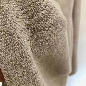 Knitted top with 3/4 sleeve. Beige-gold colour. Length 74 cm. Little used.