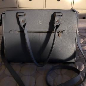 Dejlig rummelig taske i støvet blå.  Rigtig god inddeling af rum og adaxs gode kvalitet.  Købt sidste sommer i Magasin for 3500kr Får den desværre ikke brugt da jeg har en mani for tasker og har rigtig mange.  Synd den bare hænger, er kun brugt få gange og er som ny.