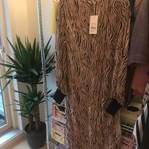 Den er ny med prismærke, men der er kommet huller bag på kjolen, helt nederst. Ses på billede 3. Derfor sælges den billigt. Man kan evt. få lagt kjolen lidt op.