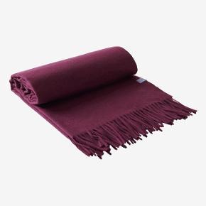 Varm, eksklusiv og luksuriøs plaid i blommefarvet kashmir og uld med frynser i enderne. Kashmir er et af de mest værdifulde naturlige tekstiler i verden.  50% kashmir og 50% uld. Størrelse: 130x170 cm Vaskeanvisning: Kemisk rens.  P R I S   5 5 0,-  (i butikken 1.900,-) Helt ny og i ubrudt emballage.  Fås også i Sort og Mørkeblå