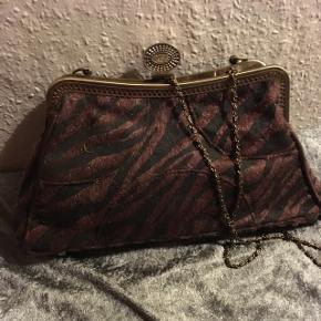 Sød lille håndtaske i dyreprint både med hank og lang kæde. Køber betaler Porto