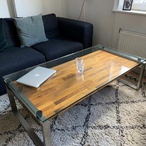 Sofabord fra Heine Design. Nypris: 14.000 Der er nogle få ridser i glaspladen.   Glasbord / træbord   Måler: 140x70   Afhentes hurtigst muligt på Frederiksberg. (Glasplade kan tages af) Bud modtages.
