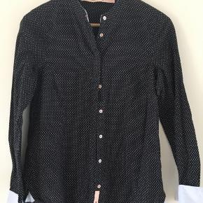 Lækker skjorte med lyseblå opslag. Nypris 599