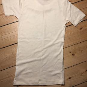 Undertøj, Uldundertrøje, Ren ny uld, str. 152/158 Med korte ærmer. Str. 152/158. Unisex. Farven er natur/råhvid og og trøjen er i 100% uld. Den er helt ny og ubrugt. Eventuel fragt lægges oveni: 38 med DAO til nærmeste posthus/butik.