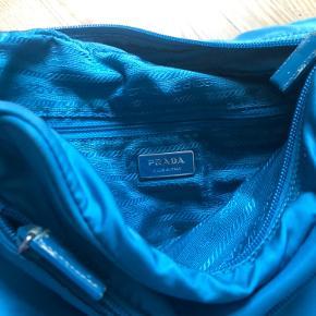 Super fed vintage Prada nylon taske. Ingen skjolder rundt på tasken. Lidt slidmærker i kanterne ved remmen og lynlåsen. Byd endelig!