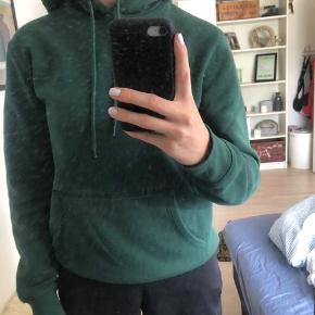 """Bløde flaskegrøn hoodie fra H&M. Det er en XS, men en str. S, vil også kunne passe den. Har sat den til """"slidt"""", da den er en lille skulle nusset, men det er ikke noget slemt. Det er vist på billede 2;)"""