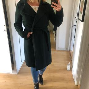 En lækker, varm frakke i god kvalitet i en flot mørkegrøn farve. Store lommer, bindebånd. Knapperne indeni er faldet ud (se sidste billede), men jeg har selv aldrig brugt dem, men blot lukket den ved hjælp af bindebåndet.