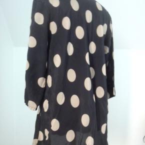 Lang bluse/tunika, sort med gyldne bomber. ½ ærme.  V-hals. Viscose. Brystvidde 104, længde 71.