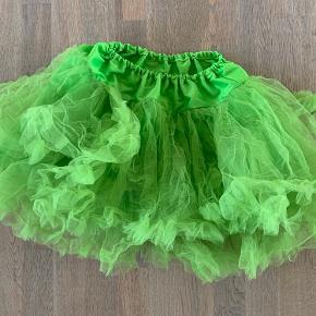 Tyl skørt i skrigende grøn med masser af lag i nederdelen og elastik i taljen. Vil passe en pige på 9-10 år. Sat under slidt da den er gået et stykke op i syning ved tyl.