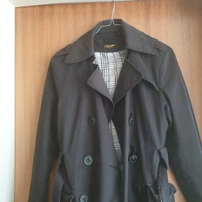 Smuk trench coat fra mærket Amazone Couture. Mangler de to nederste knapper, så derfor er den kategoriseret som slidt. Ud over dette, er den i super kvalitet!