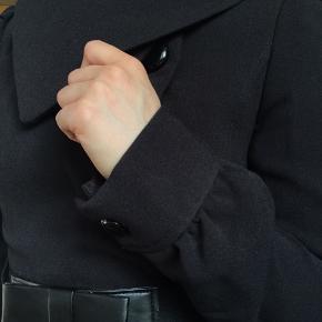 Pæn trenchcoat inspireret sort jakke fra H&M. Flot, figursyet med elastisk bælte der lukkes med trykknapperne foran under sløjfen. Bell sleve effekt, skjulte lommer, blødt stof. Let frakke der kan bruges næsten hele året, forår/sommer/efterår.  Mærkerne er taget af, men den har ikke været brugt. 200mp, ellers kom med et bud.  Obs: et par af billederne er overeksponerede for at kunne se teksturen af stoffet bedre, men den er altså sort:-)  Kan give mængderabat ved køb af mere end én ting.