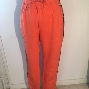 Orange joggingbukser fra human with attitude i størrelse medium - med sort logo bånd nedad hvert ben. Elastik i livet og forneden.