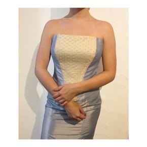 Todelt gallakjole med nederdel og corsage.  Corsagen er med snører i ryggen, og størrelsen kan dermed varieres.  Sættes er skræddersyet.  Samlet pris 600 kr