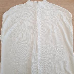 Hvid T-shirt med høj hals og uden ærmer. Lynlås og knaplukning i ryggen. Fejler intet.