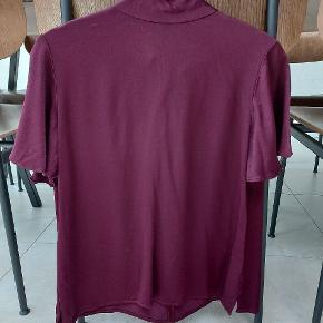 Smuk bluse fra Zara i en flot dyb blomme farve. Str XS. Har binde sløjfe i nakken. Står som ny. Stoffet er satin aktivt.