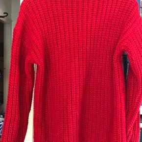 """Højrød sweater i patentstrikning med en lille rullekrave. Mærket står som """"Stile Benetton"""". 50% uld og 50% acryl. Prisen er ekskl. porto."""