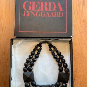Halskæde lavet i mørk horn fra Gerda Lynggaard pour Monies.  Den er fra omkring 1990 men er kun brugt få gange.
