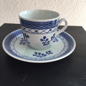 Royal Copenhagen Blå Tranquebar fajancestel i gråblå glasur dekoreret med håndmalet blå blomst og blå bånd. 1 sortering. Pris for underkop, kop og side tallerken 125. Jeg har 8 sæt