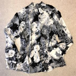 Skjorte / tunika fra Zeze.  I sort-hvide-og-grå farver.  Fine flæse- og knapdetaljer på ærmerne.  Materialet er polyester i god, organza-lignende kvalitet.  Størrelse L. Omkreds ca. 110 cm. Passer mindst str. M-xL  Har været brugt og vasket en enkelt gang.  Nypris 299 kr.  Sælges for 45 kr. + evt. porto.  Kan afhentes på Frederiksberg.